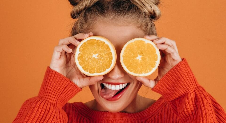 woman holding orange slices in front of her eyes to represent audience segmentation